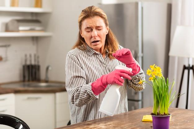 Rijpe huisvrouw met roze handschoenen die niest en allergisch is voor chemicaliën