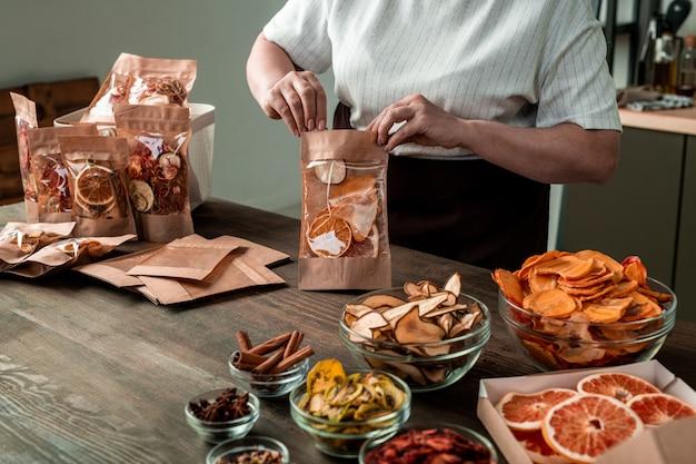 Rijpe huisvrouw verpakt gedroogde sinaasappels, peren, dadelpruimen, kiwi en aardbeien in papieren pakjes per keukentafel