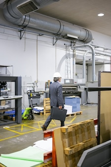 Rijpe ingenieur in formeel pak en bouwvakker die op fabrieksvloer loopt, draagtas met gereedschap