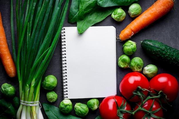 Rijpe ingrediënten en blanco receptenboek voor het koken van verse salade en groentegerechten. goede voeding, gezond uitgebalanceerd voedsel. dieet plan. schoon en gezond eten. kopieer ruimte