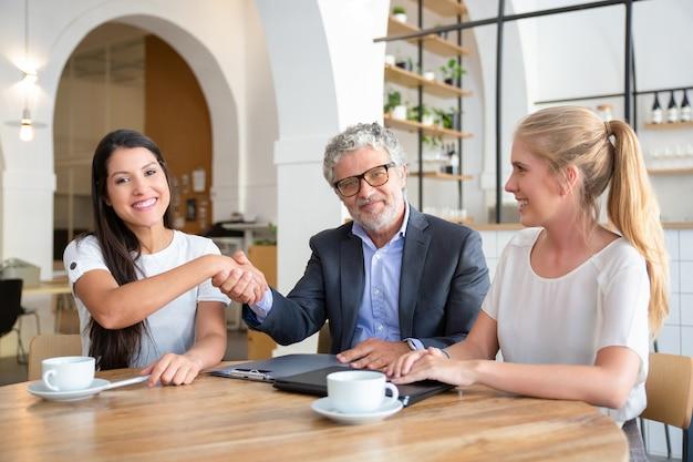 Rijpe investeerder handen schudden met jonge ondernemers