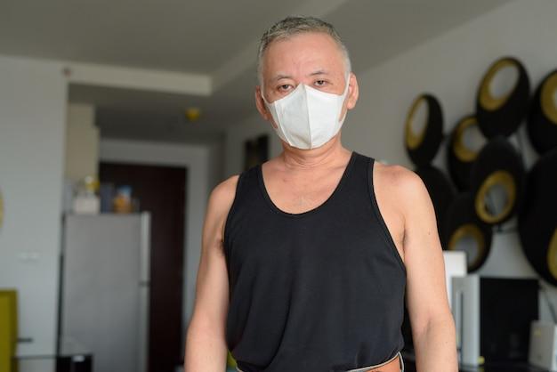 Rijpe japanse mens die masker thuis onder quarantaine dragen wegens covid-19 pandemie