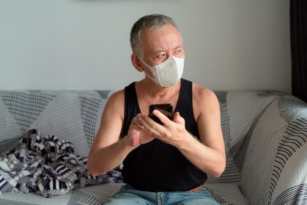 Rijpe japanse mens die met masker terwijl het gebruiken van telefoon thuis onder quarantaine denken