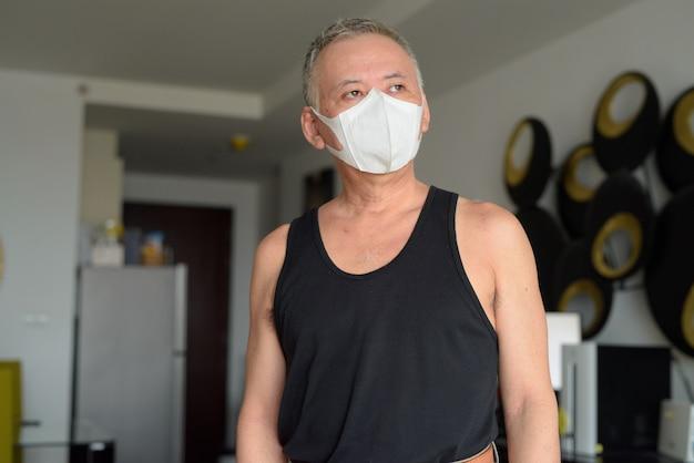 Rijpe japanse mens die met masker thuis onder quarantaine denken wegens covid-19 pandemie