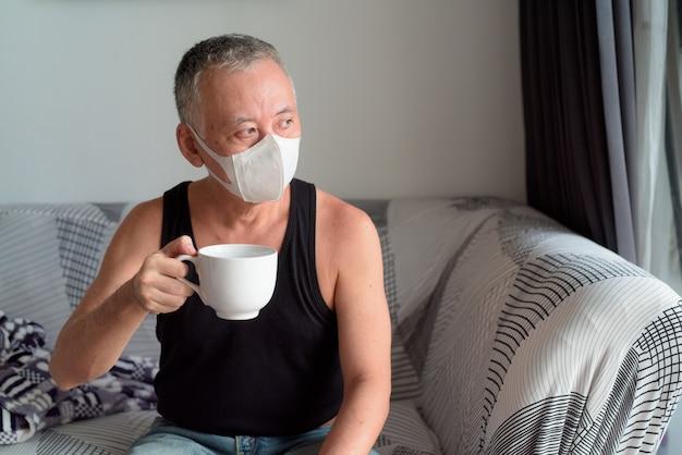Rijpe japanse mens met masker die en thuis koffie onder quarantaine denken drinken