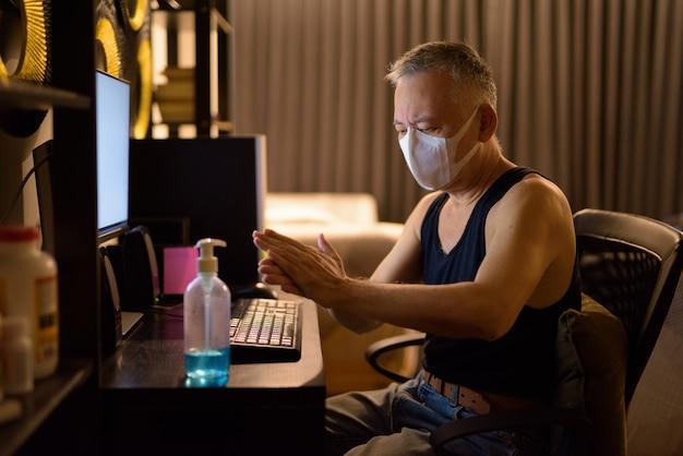 Rijpe japanse mens met masker die handdesinfecterend middel gebruiken terwijl thuis het overwerk werken