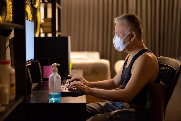 Rijpe japanse mens met masker die overwerk thuis werken