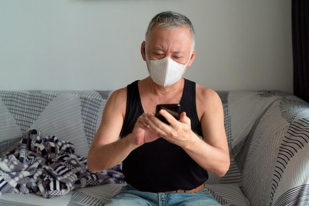 Rijpe japanse mens met masker die telefoon thuis onder quarantaine met behulp van