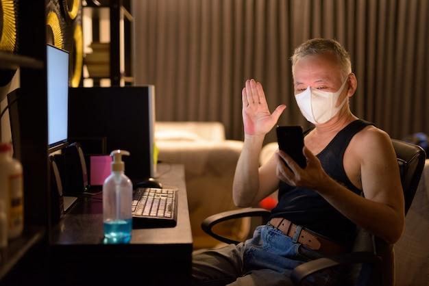 Rijpe japanse mens met masker videobellen met telefoon terwijl thuis het werken van overwerk