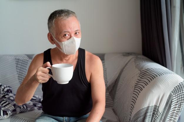 Rijpe japanse mens met maskerzitting en thuis het drinken van koffie onder quarantaine