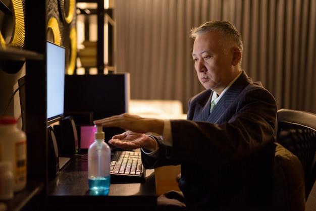 Rijpe japanse zakenman die handdesinfecterend middel gebruiken terwijl overwerk thuis laat bij nacht