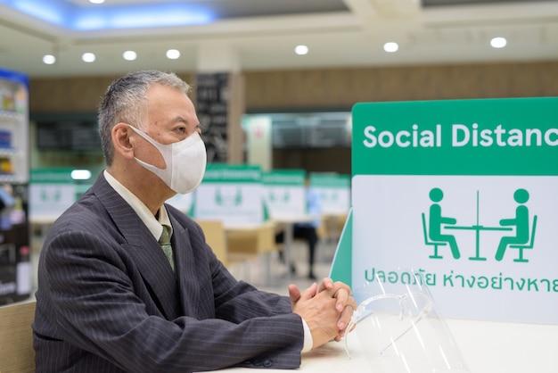 Rijpe japanse zakenman die masker draagt en met afstand bij de voedselhof zit
