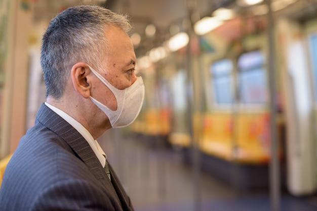 Rijpe japanse zakenman die masker draagt en met afstand binnen de trein zit