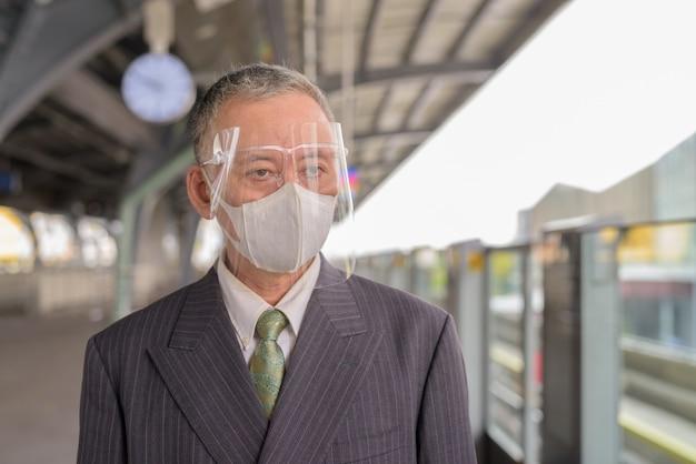 Rijpe japanse zakenman die met masker en gezichtsschild bij de skytrainpost wacht