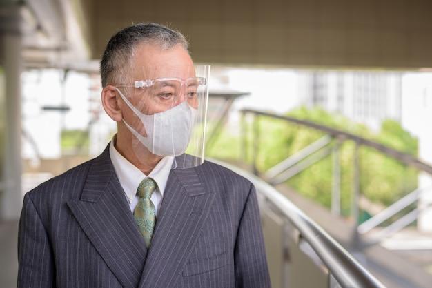 Rijpe japanse zakenman die met masker en gezichtsschild bij de voetgangersbrug denken