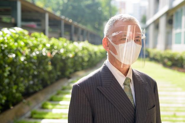 Rijpe japanse zakenman die met masker en gezichtsschild bij het park denken