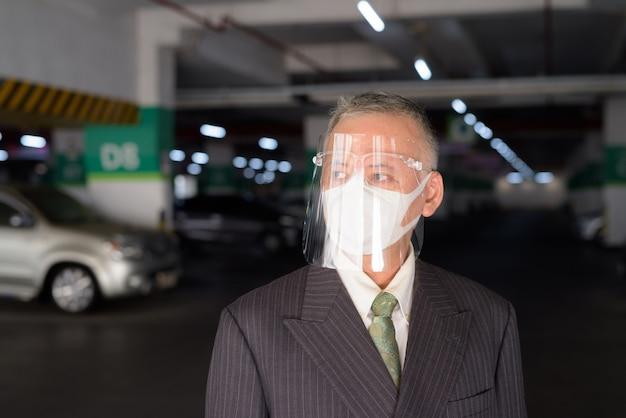 Rijpe japanse zakenman die met masker en gezichtsschild bij het parkeerterrein denken