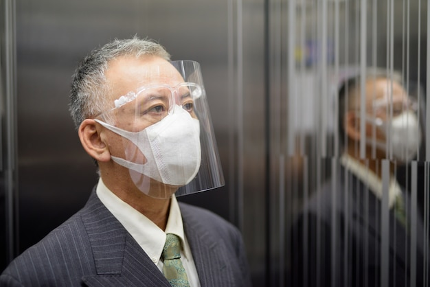 Rijpe japanse zakenman die met masker en gezichtsschild binnen de lift denken