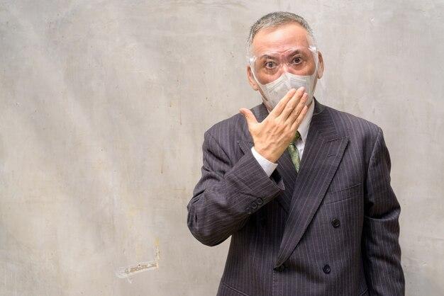 Rijpe japanse zakenman die met masker en gezichtsschild geschokt kijkt