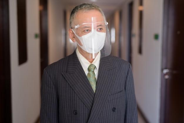 Rijpe japanse zakenman die met masker en gezichtsschild in de gang denkt