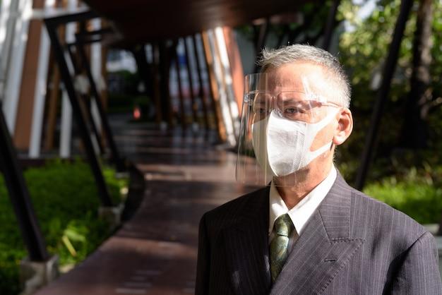 Rijpe japanse zakenman die met masker en gezichtsschild in openlucht denken