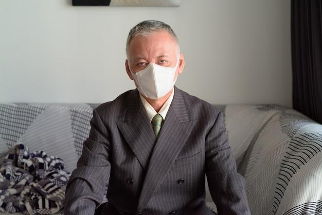 Rijpe japanse zakenman die met masker thuis onder quarantaine blijven