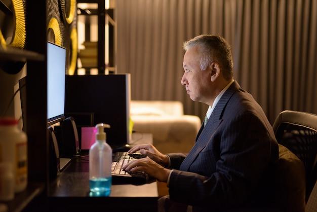 Rijpe japanse zakenman die overwerk thuis laat bij nacht werken