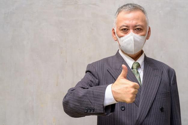 Rijpe japanse zakenman met masker die duimen in openlucht opgeven