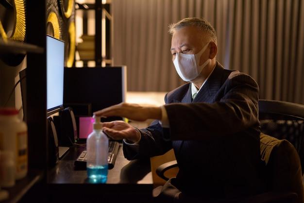 Rijpe japanse zakenman met masker die handdesinfecterend middel gebruiken terwijl overwerk thuis laat bij nacht