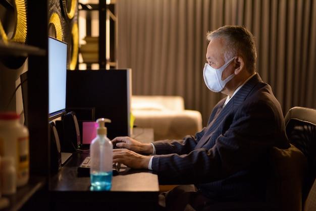 Rijpe japanse zakenman met masker die overwerk thuis laat bij nacht werken