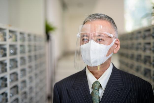 Rijpe japanse zakenman met masker en gezichtsschild bij de brievenbus