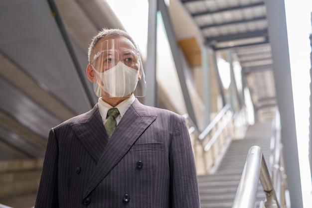 Rijpe japanse zakenman met masker en gezichtsschild die de trap naar beneden gaan