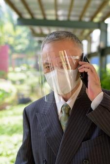 Rijpe japanse zakenman met masker en gezichtsschild die op de telefoon bij het park spreken
