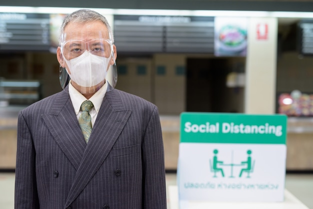 Rijpe japanse zakenman met masker en gezichtsschild het sociale distantiëren bij voedselhof