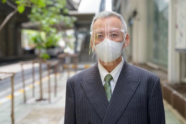 Rijpe japanse zakenman met masker en gezichtsschild in de stad