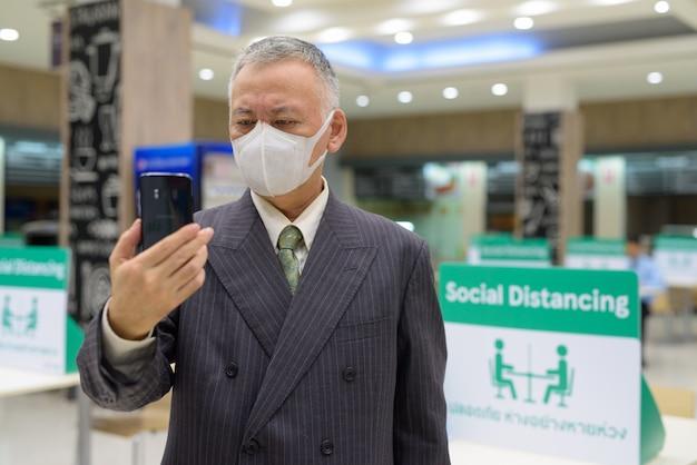 Rijpe japanse zakenman met masker gebruikend telefoon en sociale afstand bij het voedselhof