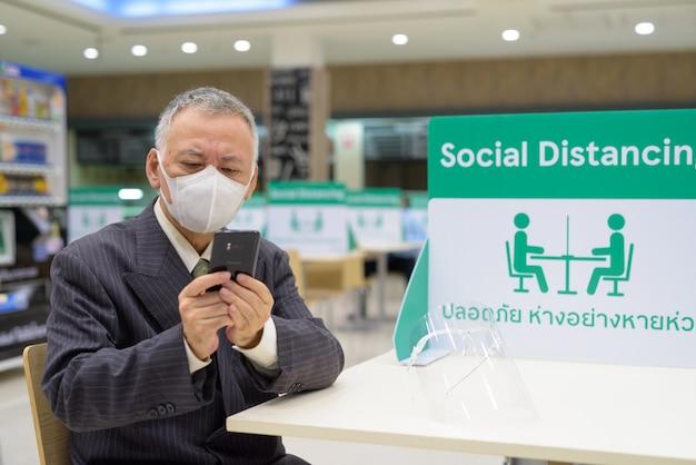 Rijpe japanse zakenman met masker gebruikend telefoon en zittend met afstand bij het voedselhof