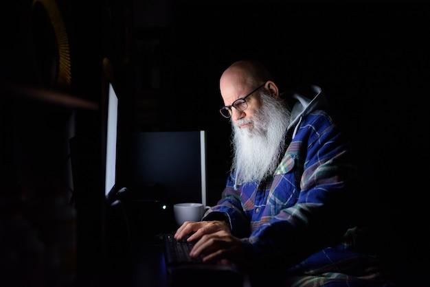 Rijpe kale bebaarde hipster man 's avonds laat overuren thuis werken