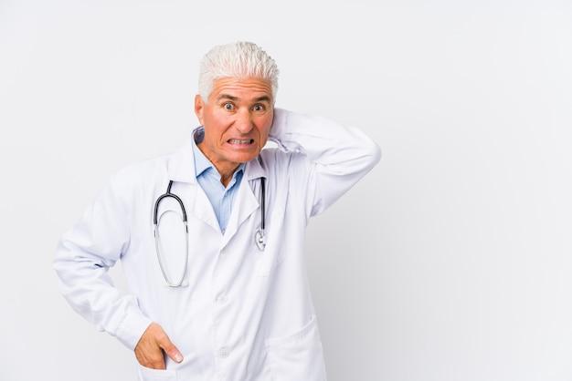 Rijpe kaukasische artsenmens die achterhoofd raakt, en een keus denkt maakt.