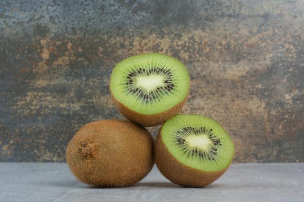 Rijpe kiwi en plakjes op stenen tafel. hoge kwaliteit foto