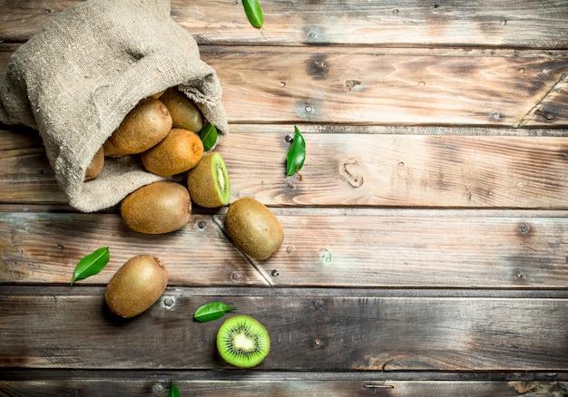 Rijpe kiwi met bladeren in een zak op rustieke lijst