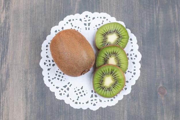 Rijpe kiwi's en plakjes op houten oppervlak