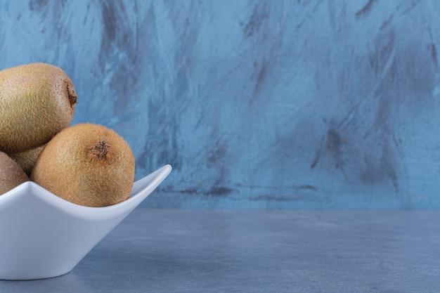 Rijpe kiwi's in een kom op marmeren tafel.