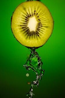 Rijpe kiwi's met druppels water geïsoleerd op groene achtergrond