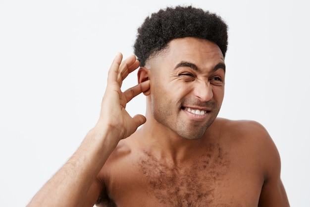 Rijpe knappe afrikaanse man met zwarte huid met krullend haar en naakte torso die 's ochtends vroeg na het bad water uit de oren probeert te halen. man klaar voor werk.