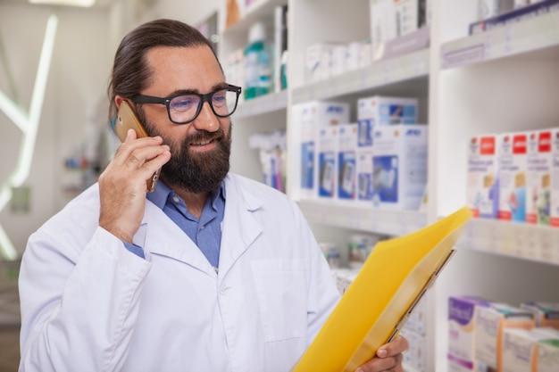 Rijpe knappe apotheker die oproepen beantwoordt, die bij drogisterij werken