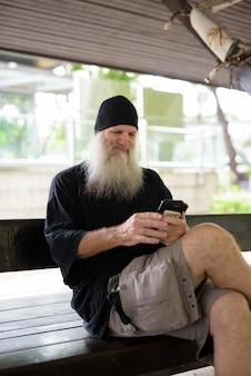Rijpe knappe bebaarde hipster man met behulp van telefoon zittend op een houten bankje