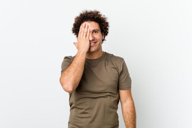Rijpe knappe mens isoleerde hebbend pret die de helft van gezicht behandelt met palm.