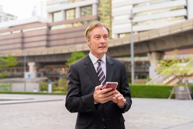 Rijpe knappe zakenman denken tijdens het gebruik van telefoon in de stad buitenshuis
