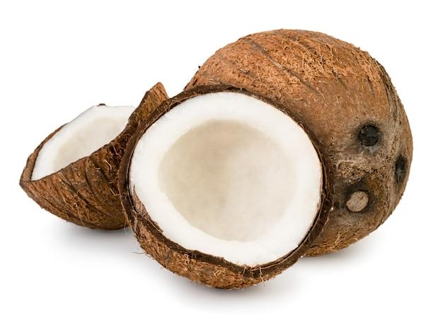 Rijpe kokosnoot en twee helften op een wit